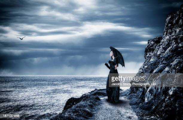pacific islander woman in black gown on cliff - rock formation stock pictures, royalty-free photos & images