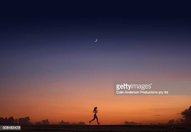 Pacific Islander woman jogging at sunset