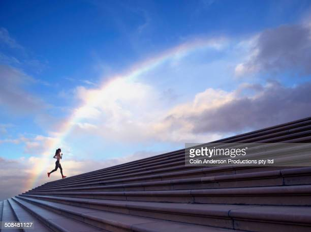 pacific islander woman jogging on concrete steps - achievement stock pictures, royalty-free photos & images
