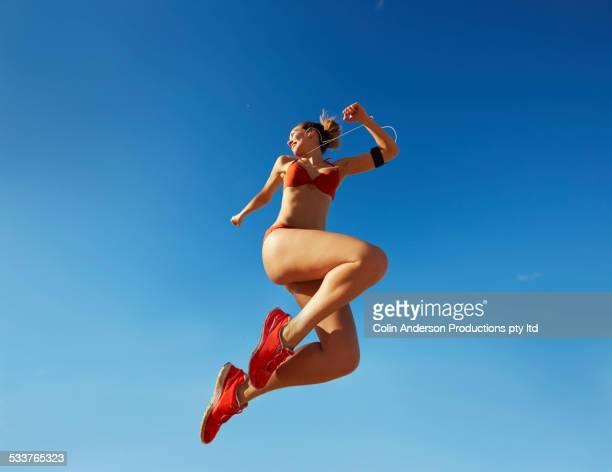 pacific islander woman jumping for joy under blue sky - ローアングル ストックフォトと画像