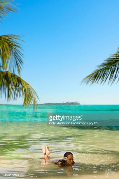 Pacific Islander woman laying in shallow ocean