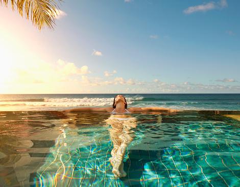 Pacific Islander woman laying in swimming pool - gettyimageskorea