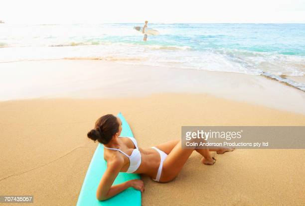 Pacific Islander woman laying on surfboard at beach