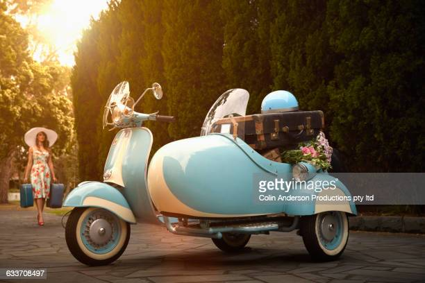 Pacific Islander woman loading suitcases in vintage scooter