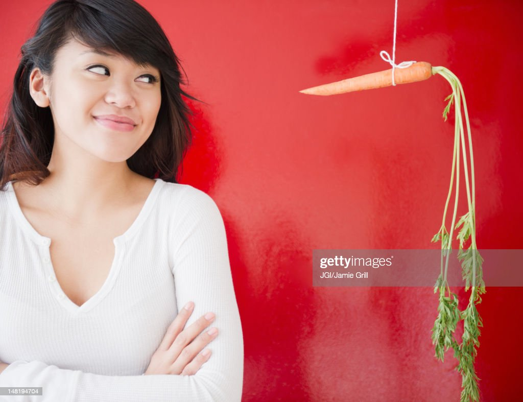 Pacific Islander woman looking at a carrot on a string : Stock Photo