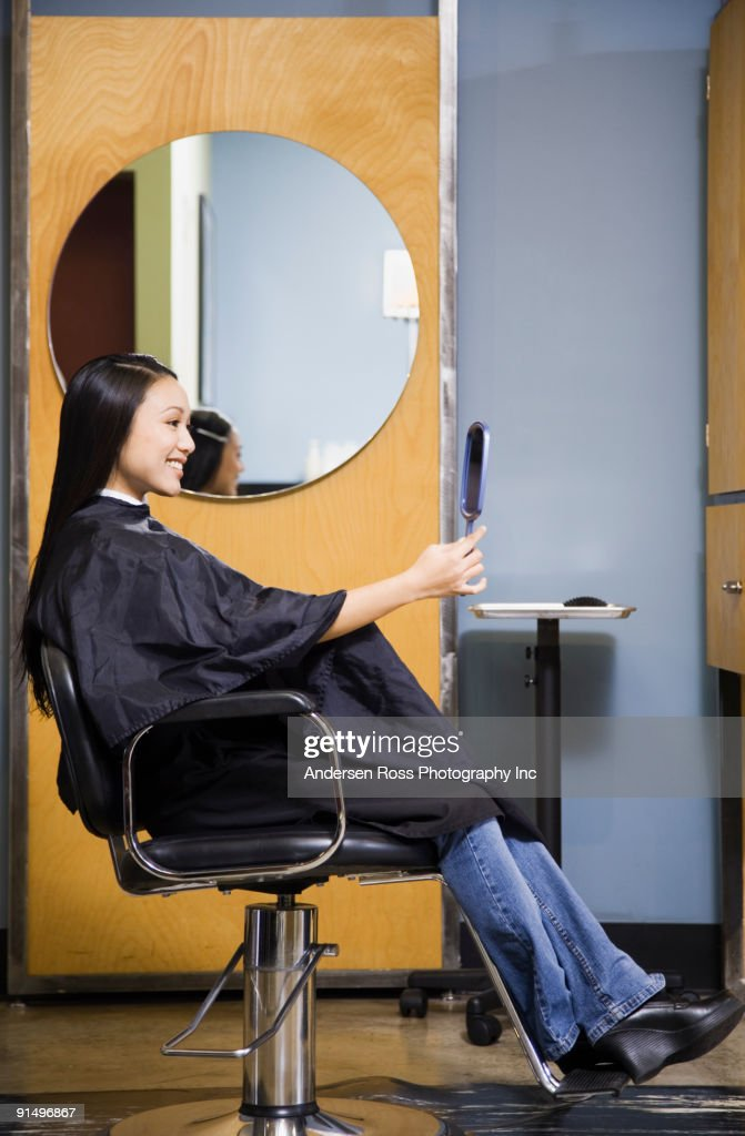 Pacific Islander woman looking at hair in salon : Stock Photo