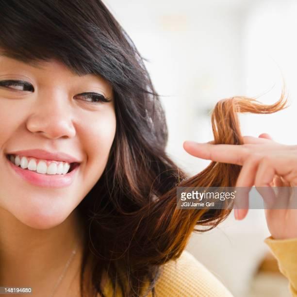 Pacific Islander woman looking at her hair