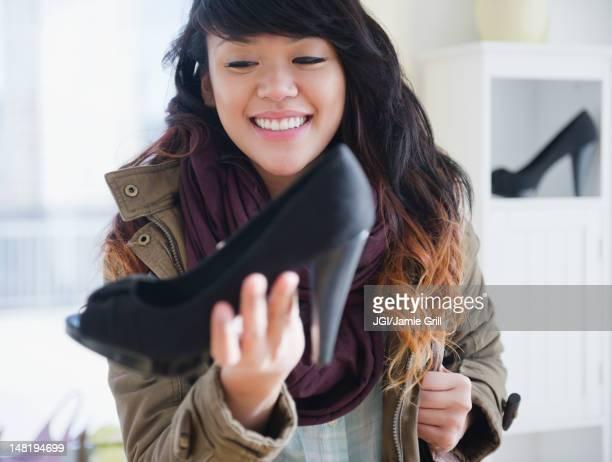 Pacific Islander woman looking at high heels in store