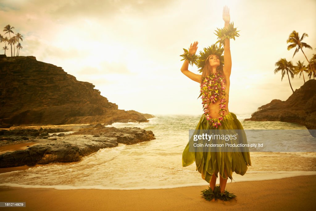 Pacific Islander woman performing traditional dance on rocky beach : Stock Photo