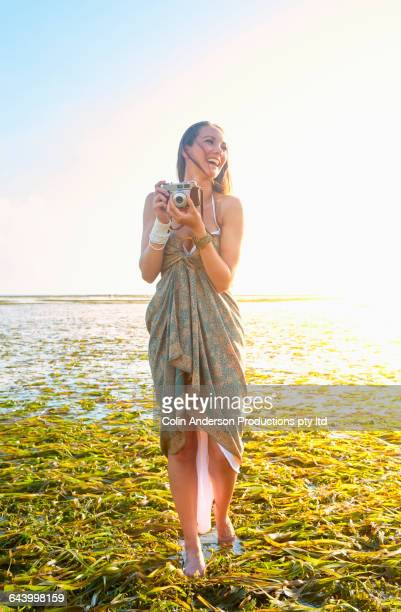 Pacific Islander woman photographing in rice paddy