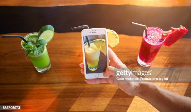 Pacific Islander woman photographing juice with cell phone