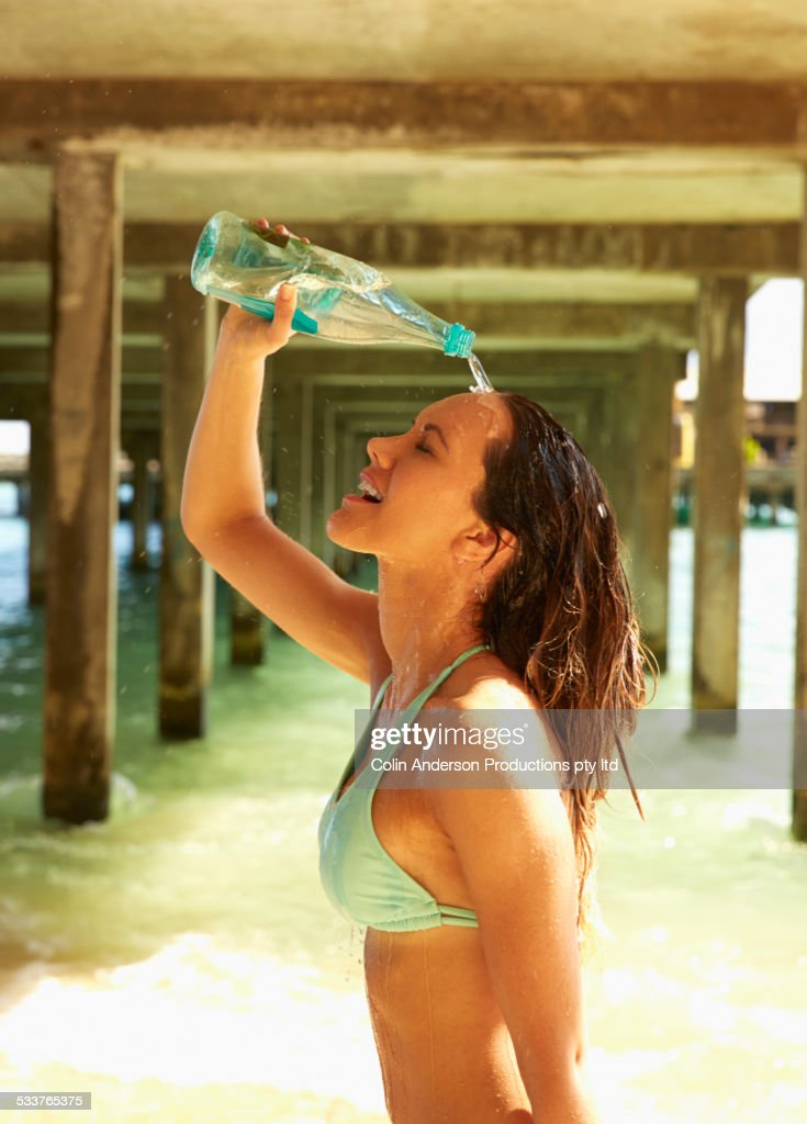 Pacific Islander woman pouring water on her head under wooden pier : Foto stock