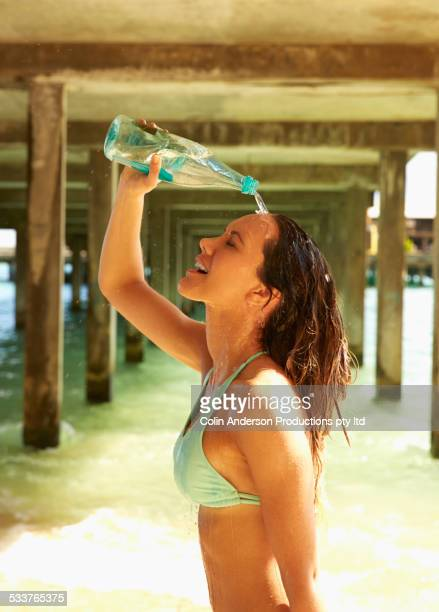 Pacific Islander woman pouring water on her head under wooden pier