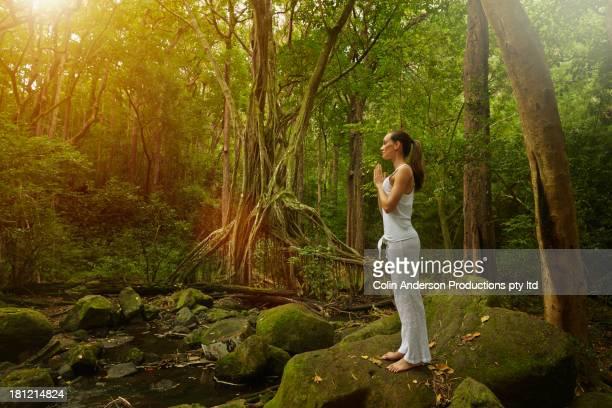 Pacific Islander woman practicing yoga in jungle