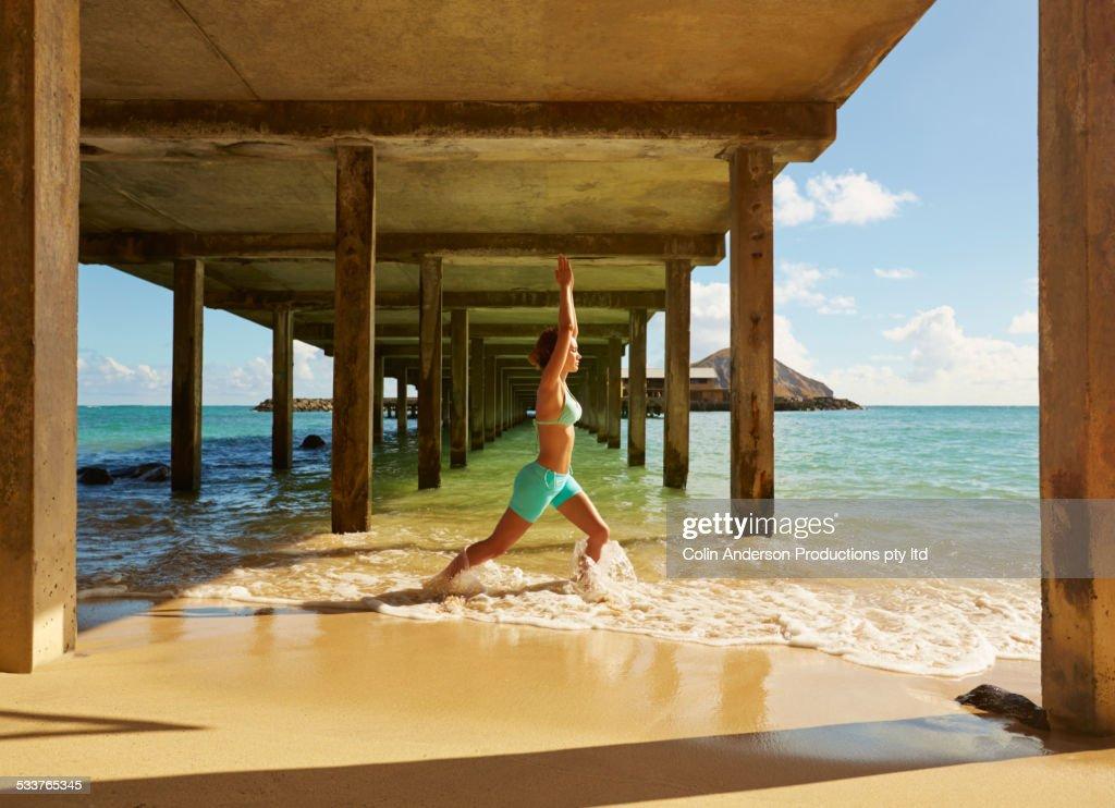 Pacific Islander woman practicing yoga under wooden pier on beach : Foto stock