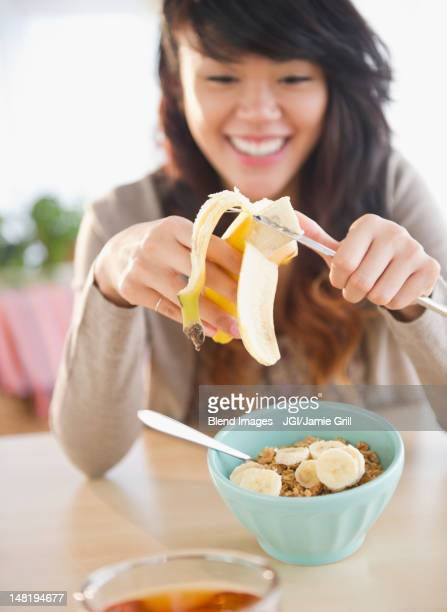 Pacific Islander woman putting bananas on cereal