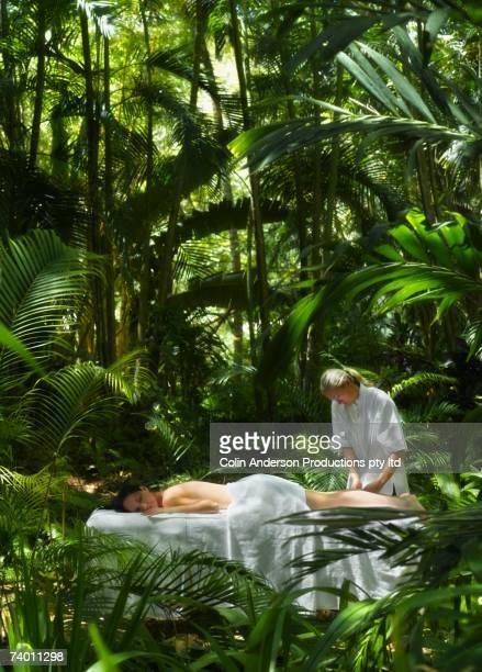 pacific islander woman receiving massage in jungle - lugar turístico fotografías e imágenes de stock