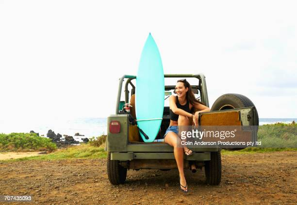 Pacific Islander woman relaxing in off-road vehicle with surfboard