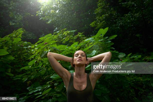 Pacific Islander woman relaxing in rainforest
