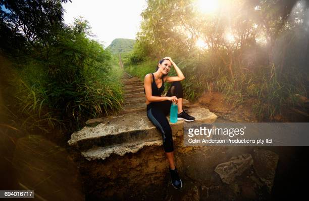 Pacific Islander woman resting on staircase on hill