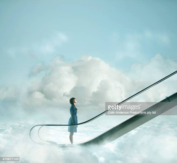 pacific islander woman riding escalator in sky - anticipation stock pictures, royalty-free photos & images