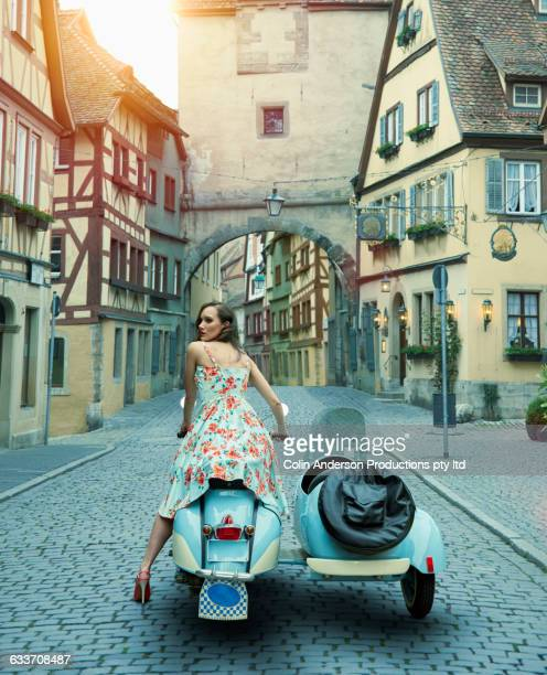 Pacific Islander woman riding vintage scooter in village