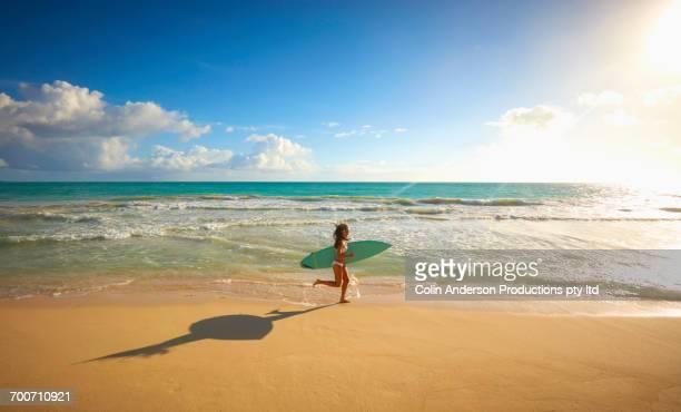 pacific islander woman running on beach carrying surfboard - ワイキキビーチ ストックフォトと画像