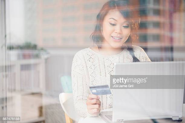 Pacific Islander woman shopping online on laptop behind window