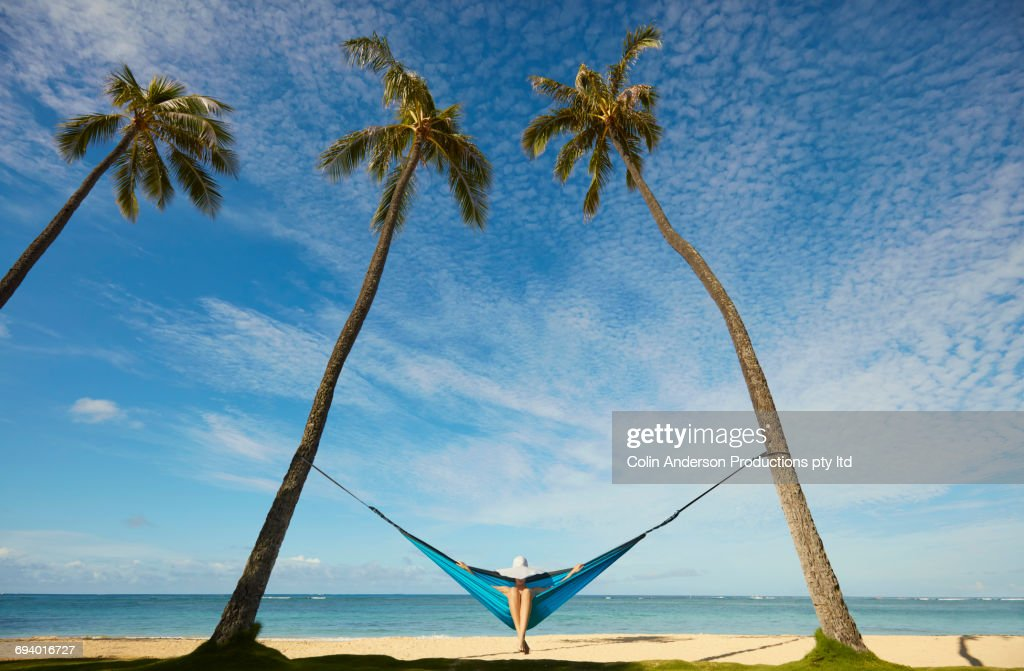 Pacific Islander woman sitting in hammock between palm trees : Stock Photo