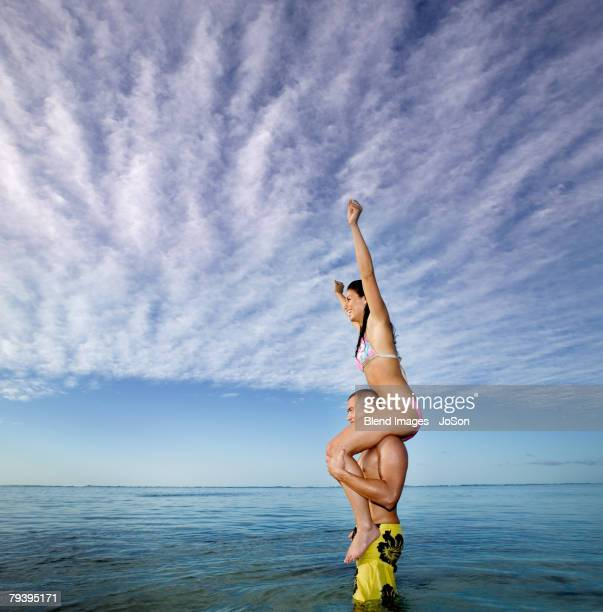 pacific islander woman sitting on boyfriend's shoulders - carrying a person on shoulders stock photos and pictures