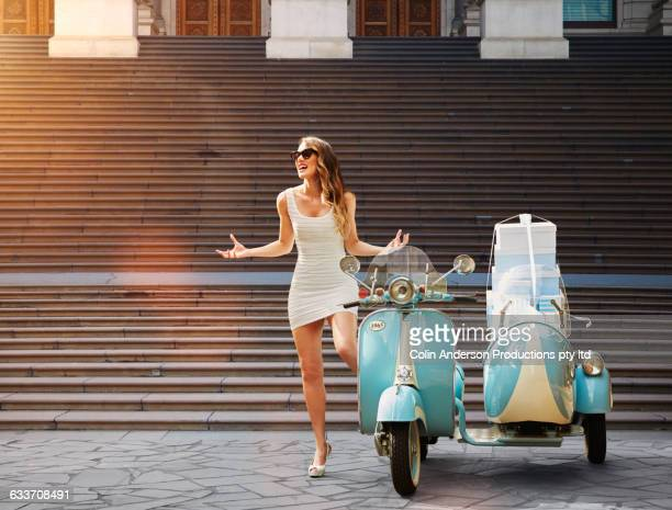 Pacific Islander woman standing near vintage scooter