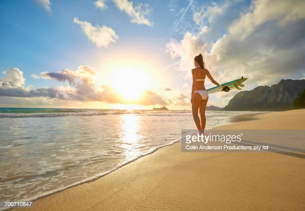 Pacific Islander woman standing on beach holding surfboard