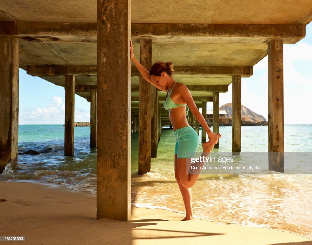 Pacific Islander woman stretching under wooden pier on beach : Foto stock