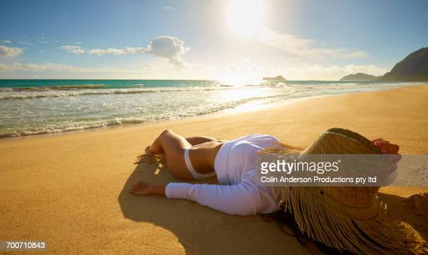 Pacific Islander woman sunbathing on beach