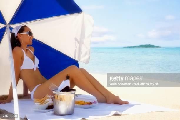 Pacific Islander woman under beach umbrella with food