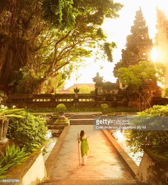 Pacific Islander woman walking at ornate ruins