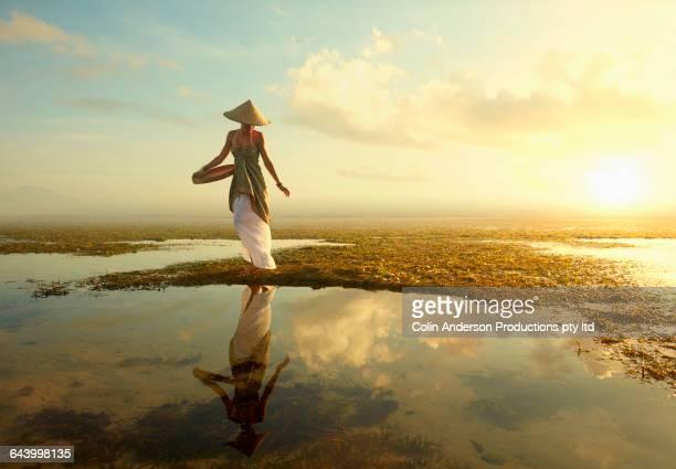 Pacific Islander woman walking in rice paddy