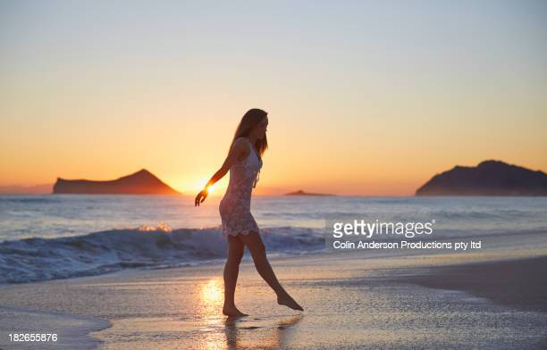 Pacific Islander woman walking in waves on beach