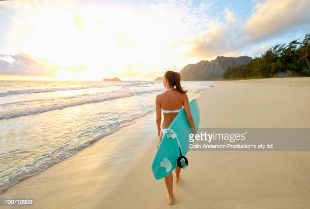 Pacific Islander woman walking on beach carrying surfboard