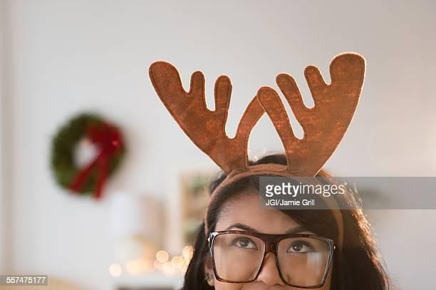 Pacific Islander woman wearing Christmas reindeer horns