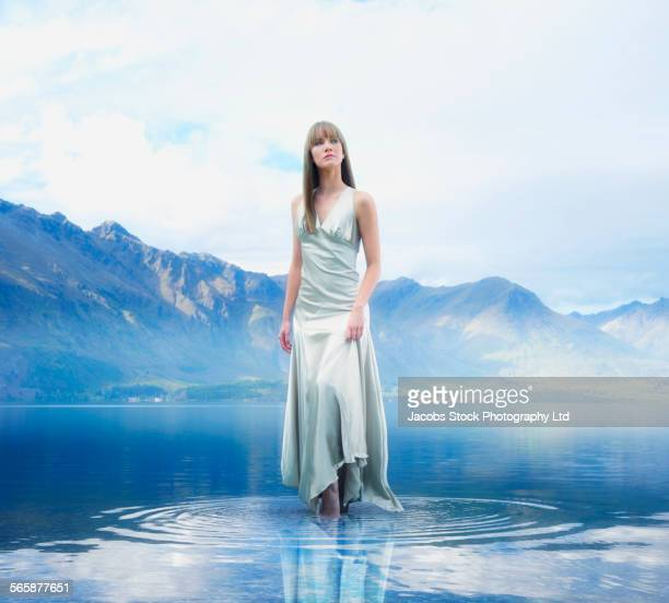Pacific Islander woman wearing evening gown in remote lake
