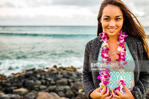 Pacific Islander woman wearing flower lei near rocky beach