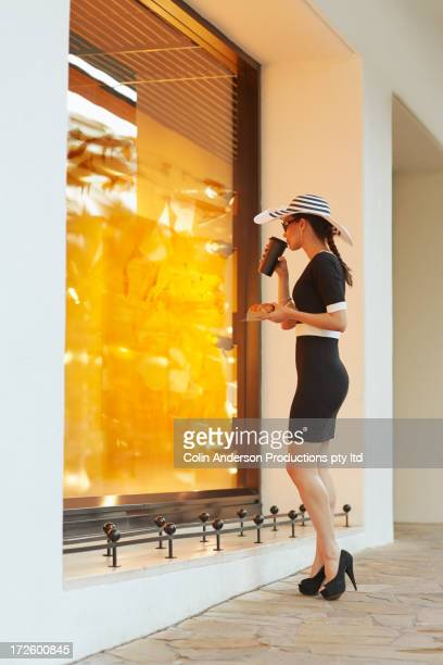 Pacific Islander woman window shopping on city street