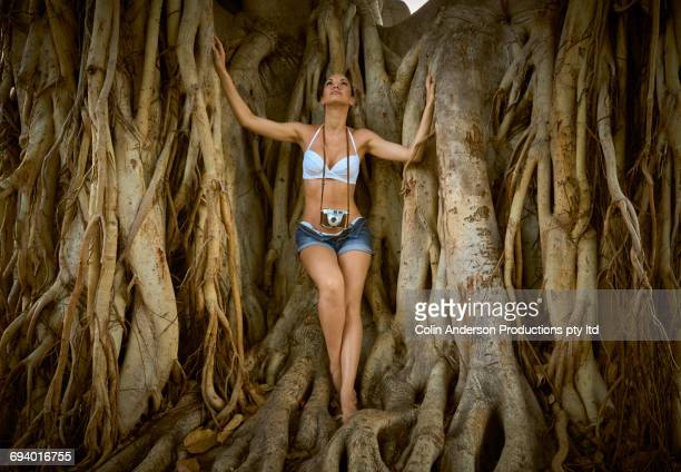 pacific islander woman with camera standing on tree roots - banyan tree stock photos and pictures
