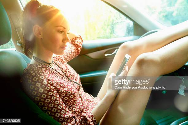 Pacific Islander woman with feet up in car texting on cell phone