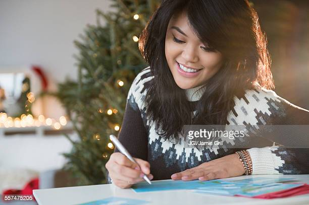 pacific islander woman writing christmas card - thinking of you card stock pictures, royalty-free photos & images
