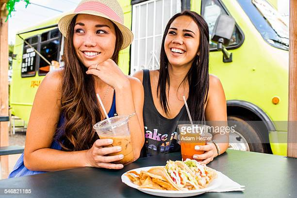 Pacific Islander women eating and drinking near food cart