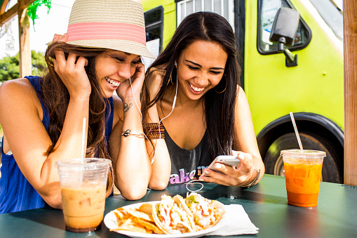 Pacific Islander women using cell phone near food cart - gettyimageskorea