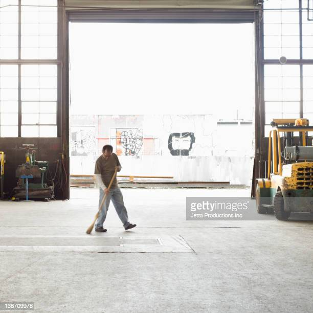 pacific islander worker sweeping warehouse - broom sweeping stock pictures, royalty-free photos & images