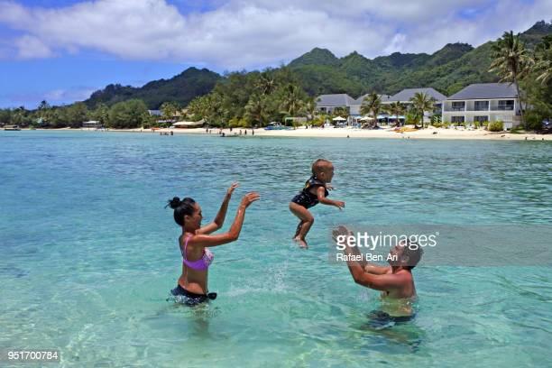 pacific islanders couple having fun with their baby boy in muri lagoon, rarotonga cook islands - rafael ben ari bildbanksfoton och bilder